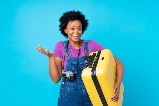Mulher afro-americana viajante com mala ao longo da parede azul