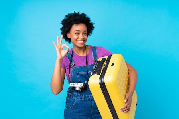 Mulher afro-americana viajante sobre parede azul