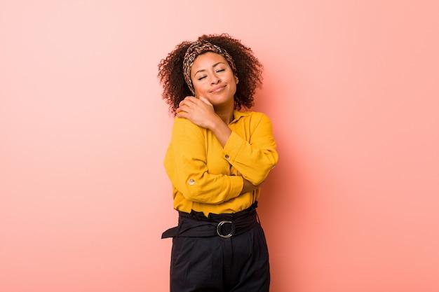 Mulher afro-americano nova contra abraços cor-de-rosa, sorrindo despreocupado e feliz.