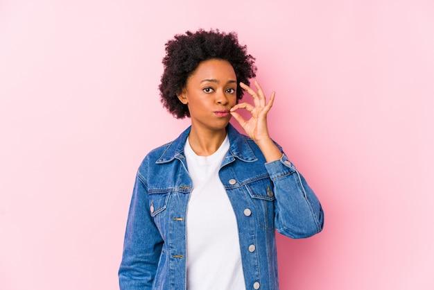 Mulher afro-americano nova contra um fundo rosa isolado com os dedos nos lábios, mantendo um segredo.