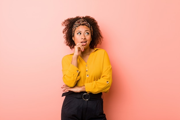 Mulher afro-americano nova contra um pensamento relaxado cor-de-rosa sobre algo que olha uma cópia.