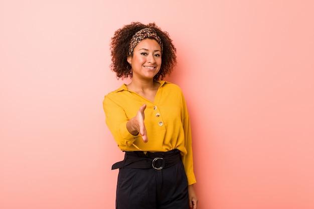 Mulher afro-americano nova contra uma parede cor-de-rosa que estica a mão no gesto de cumprimento.