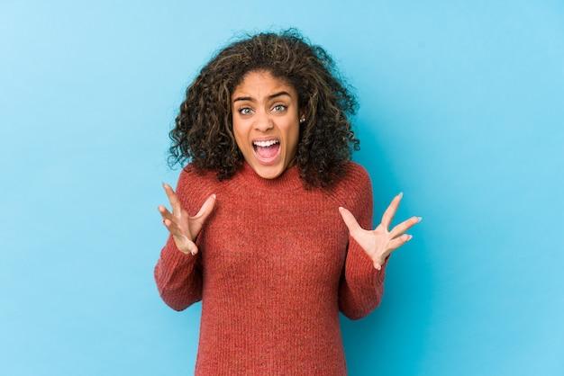 Mulher afro-americano nova do cabelo encaracolado que grita com raiva.