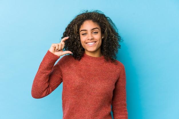 Mulher afro-americano nova do cabelo encaracolado que guarda algo pequeno com o dedo indicador, sorrindo e confiante.