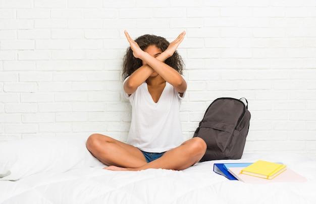 Mulher afro-americano nova do estudante na cama que mantém dois braços cruzados, conceito da negação.
