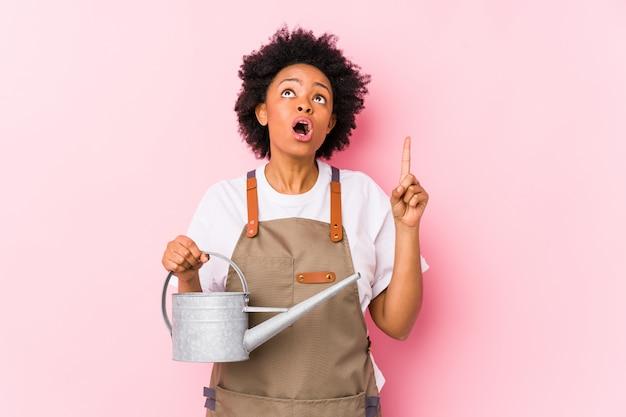 Mulher afro-americano nova do jardineiro que aponta de cabeça com boca aberta.