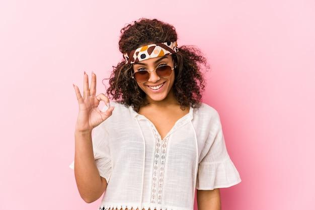 Mulher afro-americano nova do moderno isolada na parede cor-de-rosa alegre e segura mostrando o gesto aprovado.