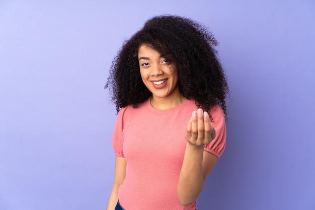Mulher afro-americano nova isolada no convite roxo para vir com mão. feliz que você veio