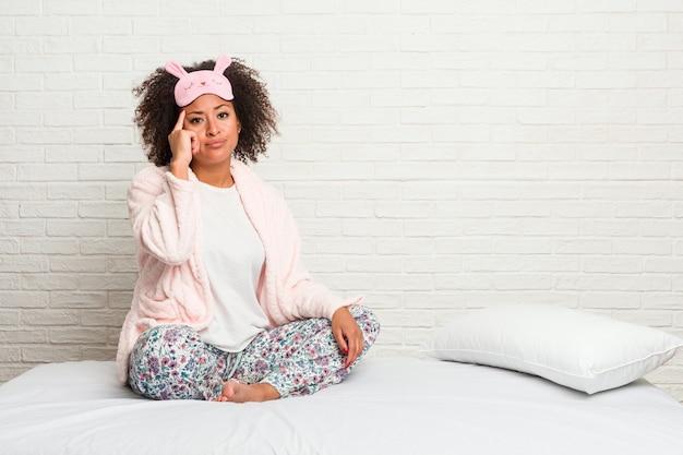 Mulher afro-americano nova na cama que veste o pijama que aponta o templo com o dedo, pensando, focalizado em uma tarefa.