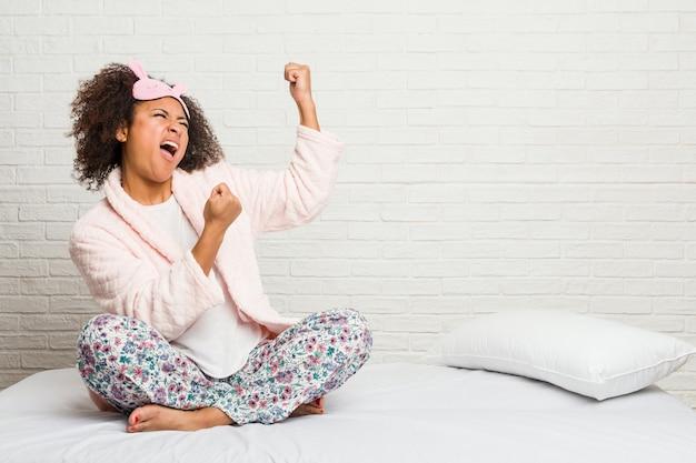Mulher afro-americano nova na cama que veste o pijama que levanta o punho após uma vitória, conceito do vencedor.