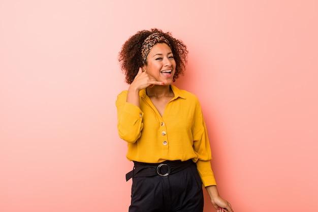 Mulher afro-americano nova no rosa que mostra um gesto de chamada de telefone móvel com dedos.