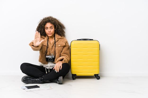 Mulher afro-americano nova pronta para uma viagem que está com a mão estendida que mostra o sinal de parada, impedindo-o.