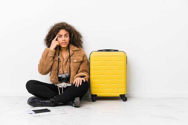 Mulher afro-americano nova pronta para uma viagem que mostra um gesto da decepção com dedo indicador.