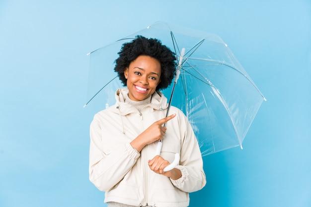 Mulher afro-americano nova que guarda um guarda-chuva que sorri e que aponta de lado, mostrando algo no espaço em branco.