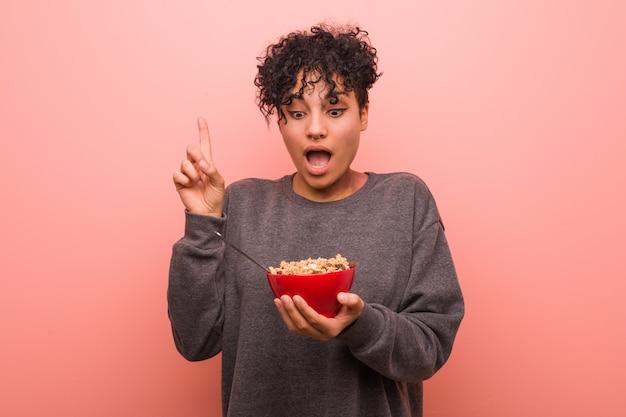 Mulher afro-americano nova que guarda uma bacia de cereal que tem alguma grande ideia, conceito da faculdade criadora.