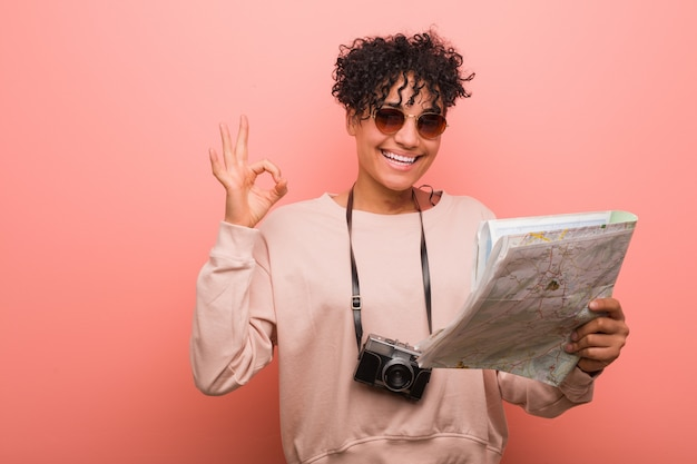 Mulher afro-americano nova que mantém um mapa alegre e seguro mostrando o gesto aprovado.