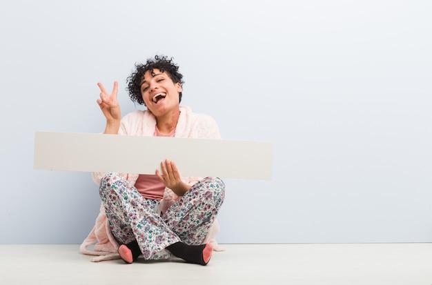 Mulher afro-americano nova que senta-se com um cartaz que mostra o número dois com dedos.