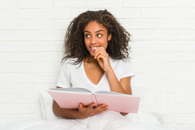Mulher afro-americano nova que senta-se na cama que estuda o pensamento relaxado sobre algo que olha um espaço da cópia.