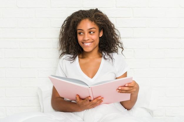Mulher afro-americano nova que senta-se na cama que estuda o sorriso seguro com braços cruzados.