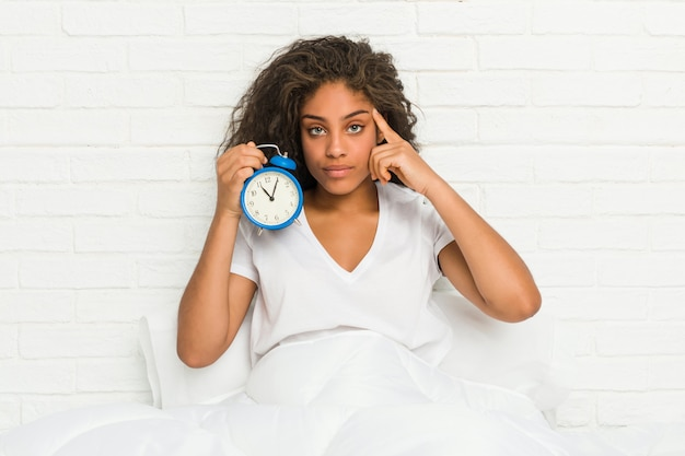Mulher afro-americano nova que senta-se na cama que guarda um despertador que aponta seu templo com o dedo, pensando, focalizado em uma tarefa.
