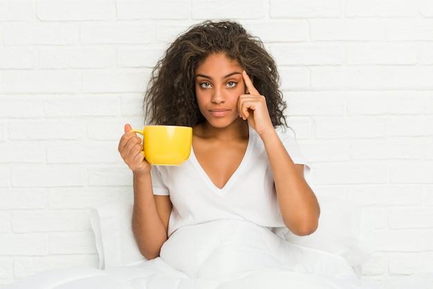 Mulher afro-americano nova que senta-se na cama que guarda uma caneca de café que aponta seu templo com o dedo, pensando, focalizado em uma tarefa.
