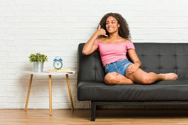 Mulher afro-americano nova que senta-se no sofá que mostra um gesto de chamada de telefone móvel com os dedos.