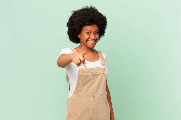 Mulher afro apontando para a câmera com um sorriso satisfeito, confiante e amigável, escolhendo seu conceito de chef