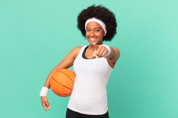Mulher afro apontando para a câmera com um sorriso satisfeito, confiante e amigável, escolhendo você. conceito de basquete