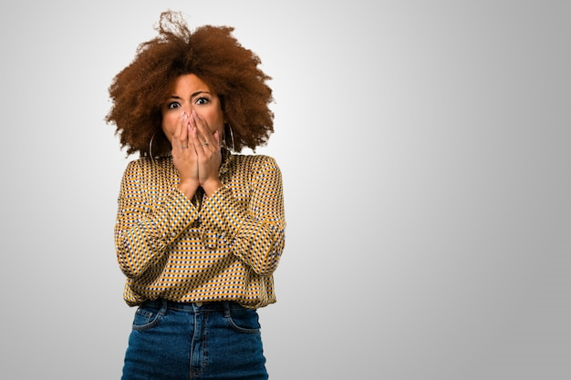 Mulher afro assustada, cobrindo a boca dela