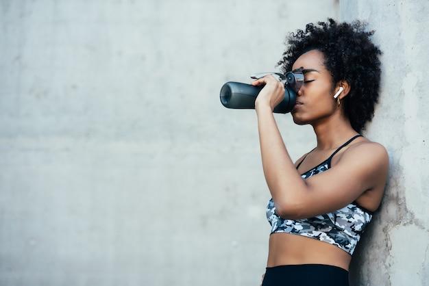 Mulher afro atlética bebendo água e relaxando depois do treino ao ar livre.
