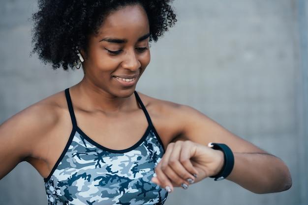 Mulher afro-atlética checando as horas no relógio inteligente enquanto faz exercícios ao ar livre