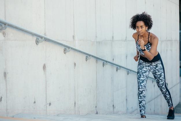 Mulher afro-atlética correndo e fazendo exercícios ao ar livre.