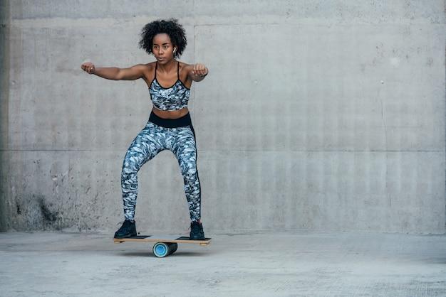 Mulher afro-atlética fazendo exercícios e agachamento com as pernas ao ar livre
