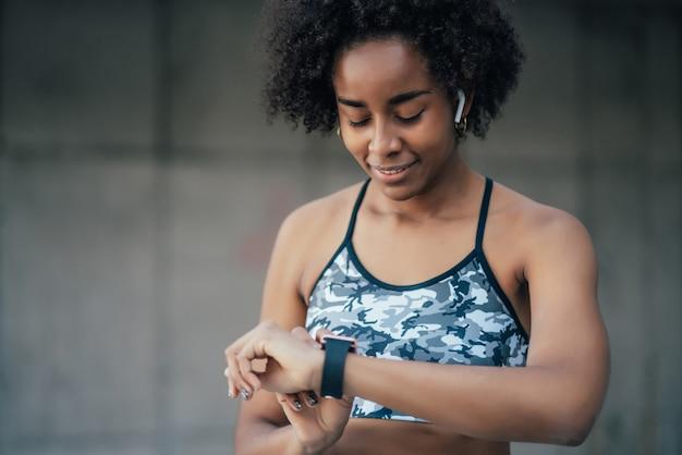 Mulher afro-atlética, verificando o tempo no relógio inteligente enquanto faz exercícios ao ar livre. esporte e conceito de estilo de vida saudável.