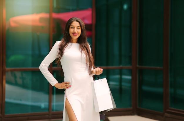 Mulher afro bonita em um lindo vestido branco segurando sacolas de papel