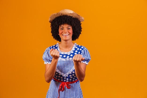 Mulher afro brasileira com roupas típicas da festa junina em amarelo