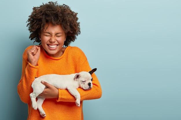 Mulher afro cheia de alegria fecha os punhos de alegria, feliz por comprar um cão de raça com pedigree desejável