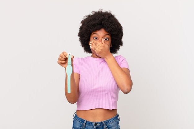 Mulher afro cobrindo a boca com as mãos com uma expressão chocada e surpresa, mantendo um segredo ou dizendo oops, conceito de relógio