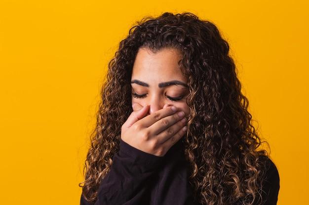 Mulher afro com a mão na boca, conceito de abuso, feminicídio, racismo e preconceito