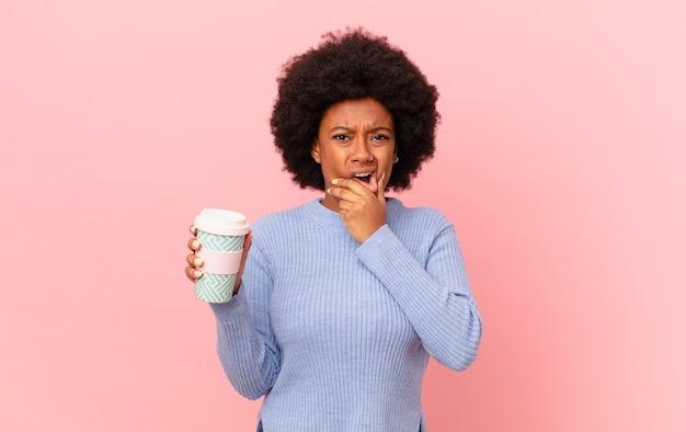 Mulher afro com boca e olhos bem abertos e mão no queixo, sentindo-se desagradavelmente chocada, dizendo o quê ou uau. conceito de café