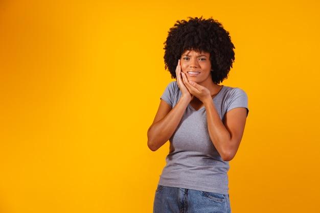 Mulher afro com dor de dente no amarelo