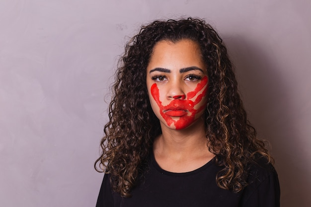 Mulher afro com marca de mão na boca em prol da conscientização do feminicídio. violência doméstica