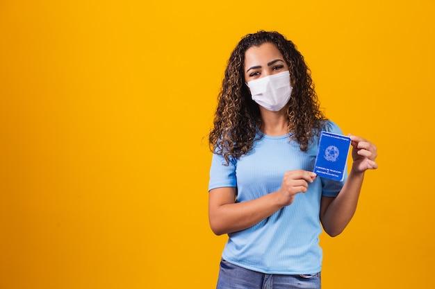 Mulher afro com máscara cirúrgica segurando cartão de trabalho brasileiro em fundo amarelo. trabalho, economia e conceito de pandemia