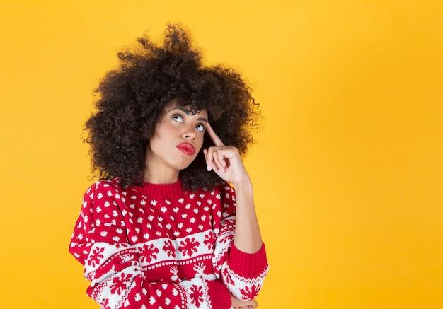 Mulher afro com roupas de natal, pensando, fundo amarelo