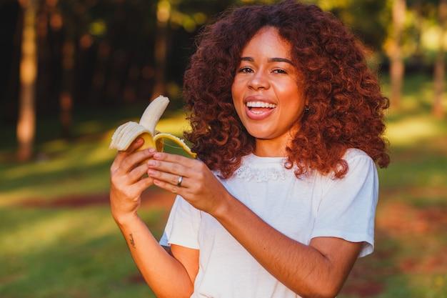 Mulher afro comendo banana no parque