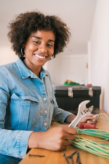 Mulher afro corrigindo problema de eletricidade em casa
