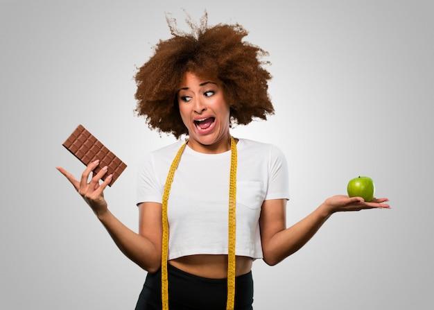 Mulher afro da aptidão nova que escolhe entre comer saudável ou o chocolate