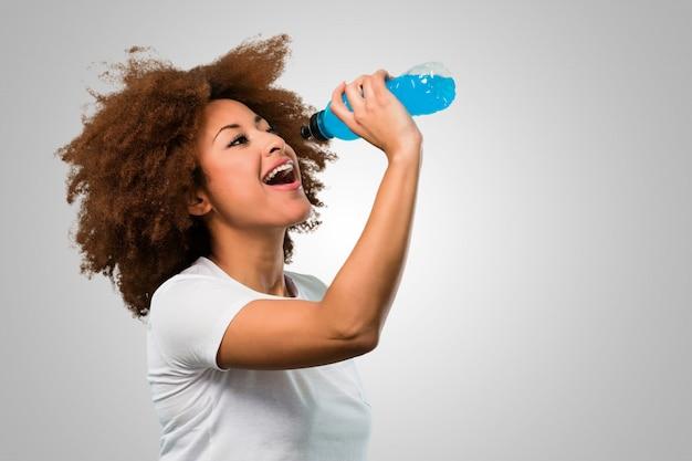 Mulher afro de aptidão jovem beber uma bebida energética