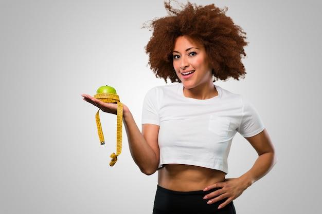 Mulher afro de aptidão jovem segurando uma maçã e uma fita métrica