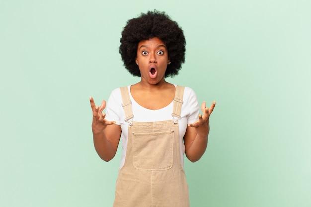 Mulher afro de boca aberta e maravilhada, chocada e atônita com um conceito incrível de chef surpresa